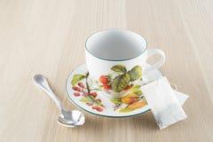 Filiżanka herbata i teaspoon na drewnianym stole Fotografia Stock