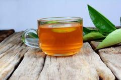 filiżanka herbata i zieleni cytryna opuszcza na starym drewnianym stole Zdjęcia Stock