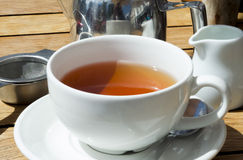 Filiżanka herbata na drewnie z kubkiem, garnkiem i durszlakiem, Fotografia Royalty Free