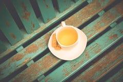 Filiżanka herbata z ciastkiem na rocznika tle Obrazy Royalty Free