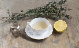 Filiżanka herbata z nowym i herbacianym durszlakiem na starym drewnianym stole Zdjęcie Royalty Free