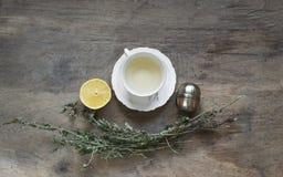 Filiżanka herbata z nowym i herbacianym durszlakiem na starym drewnianym stole Obraz Stock