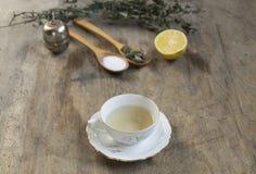 Filiżanka herbata z nowym i herbacianym durszlakiem na starym drewnianym stole selec Obrazy Stock