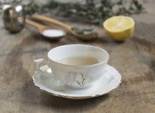 Filiżanka herbata z nowym i herbacianym durszlakiem na starym drewnianym stole selec Fotografia Royalty Free
