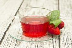 Filiżanka herbata z truskawkami na drewnianym stole Zdjęcie Royalty Free
