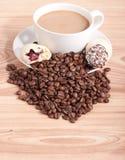 Filiżanka i kawowe fasole, cukierki na drewnianym tle Zdjęcia Royalty Free