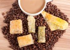 Filiżanka i kawowe fasole, cukierki na drewnianym tle Obrazy Royalty Free