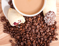 Filiżanka i kawowe fasole, cukierki na drewnianym tle Fotografia Stock