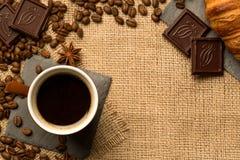 Filiżanka, kawowe fasole, czekolada, croissant, cynamon na burlap Odgórny widok obraz stock