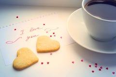 Filiżanka kawy, ciastka w formie serca i deklaracja, Obrazy Royalty Free