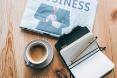 Filiżanka kawy, gazeta i notatnik na stole, Fotografia Stock