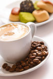 Filiżanka kawy i cukierki na spodeczku obraz stock