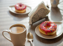 Filiżanka kawy i donaughts na stole obrazy royalty free