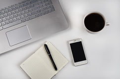 Filiżanka kawy i laptop na bielu stole zdjęcie royalty free