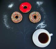 Filiżanka kawy i trzy kolorowego donuts Fotografia Royalty Free