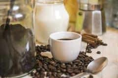 Fili?anka kawy, mleko, cynamon i niekt?re kawowe fasole na drewnianym stole w nieociosanej kuchni, pusta kopii przestrze? obraz royalty free