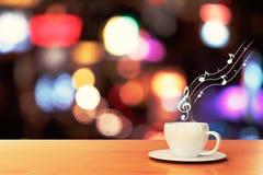 Filiżanka kawy na drewnianym stole w muzykalnych notatkach i kawiarni Zdjęcie Royalty Free