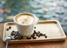 Filiżanka kawy na drewnianym stole z kawowymi fasolami Fotografia Stock