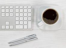 Filiżanka kawy na górze biurowego desktop Zdjęcia Royalty Free