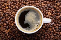 Filiżanka kawy na kawowych fasoli tle Fotografia Royalty Free
