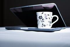 Filiżanka kawy na laptopie Ciemny pokaz Fotografia Royalty Free