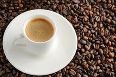 filiżanka kawy talerz na kawowych fasoli tle i kawa espresso Obrazy Royalty Free