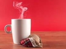Filiżanka kawy z dymem i serce na drewnianym biurku na czerwieni Zdjęcie Stock
