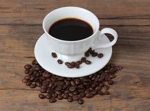 Filiżanka kawy z kawowymi fasolami Zdjęcia Stock