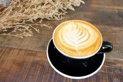 Filiżanka latte kawa z kwiatami na stole Obrazy Stock
