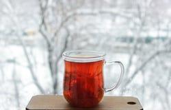 Filiżanka lipowa herbata przed okno Zdjęcia Stock