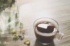 Filiżanka lub herbata, szklanej wazy kwiatu susi ziele na drewnianym stole, Zdjęcie Stock