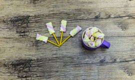 Filiżanka marshmallows z kijami na drewnianym tle fotografia royalty free
