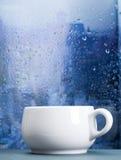 Filiżanka na deszczowym dniu przed okno Obraz Royalty Free