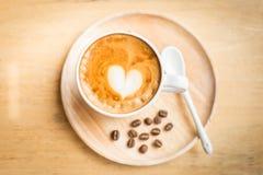 Filiżanka sztuki latte kawa z kawowymi fasolami na drewno stole Zdjęcia Royalty Free