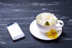 Filiżanka, telefon komórkowy i wodna leluja na drewnianym tle, fotografia royalty free