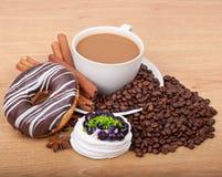 Filiżanka z kawowych fasoli ans cukierki tortem na drewnianym tle Zdjęcie Stock