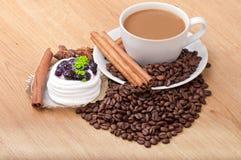 Filiżanka z kawowych fasoli ans cukierki tortem na drewnianym tle Zdjęcie Royalty Free