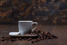 Filiżanka z spodeczkiem i kawowymi fasolami Fotografia Royalty Free