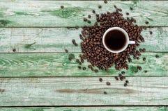 Filiżanki kawa z fasolami na zielonym drewno stole Nieociosana drewniana tekstura Zdjęcia Royalty Free