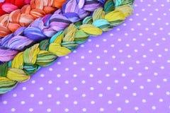 Fili del ricamo dei colori differenti su un fondo porpora Immagini Stock