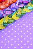 Fili del ricamo dei colori differenti su un fondo porpora Immagini Stock Libere da Diritti