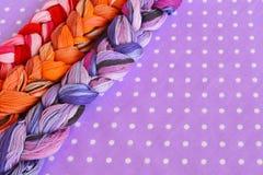 Fili del ricamo dei colori differenti su un fondo porpora Fotografia Stock