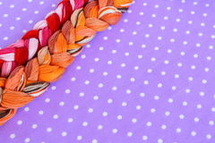 Fili del ricamo dei colori differenti su un fondo porpora Immagine Stock Libera da Diritti