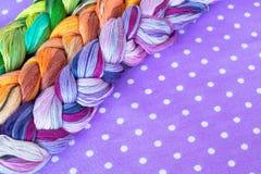 Fili del ricamo dei colori differenti su un fondo porpora Fili colorati del ricamo Fotografia Stock Libera da Diritti