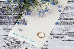 Filialen av glömma-mig-nots på papper med uttryck minns mig Fotografering för Bildbyråer