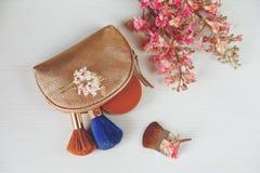 Filialer av det kastanjebruna trädet, bronspulver; Sminkborstar i den guld- kosmetiska påsen är på den vita tabellen, bästa sikt Royaltyfri Bild
