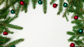 Filialer av en julgrangräns på en sida på tre sidor med röda och gröna bollar på en vit bakgrund royaltyfria foton