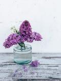 Filialer av lilan i genomskinlig glass vas på trätabellen Arkivbild