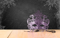 Filigree Mysterious Venetian masquerade mask on wooden table and texture black background  with snowflake overlay Royalty Free Stock Photos