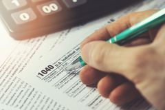 Filing annual usa individual income tax return form 1040. Hand filing annual usa individual income tax return form 1040 royalty free stock images